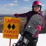 Athlete Leader, Carmen Houston-Ludlam standing next to a caution expert terrain sign while all bundled up in her snow gear while holding her snowboard